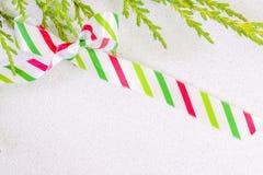 在丝毫的一把弓栓的白色,红色和绿色镶边丝绸丝带 库存照片