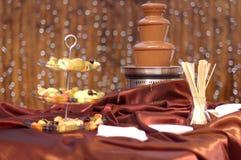 在丝绸桌布的巧克力喷泉在餐馆 免版税库存图片