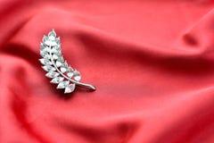 在丝绸背景的时髦的别针 免版税图库摄影