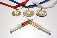 在两个五颜六色的注射器的普遍的类固醇作为一掺杂在白色背景的三枚金牌附近 免版税库存图片