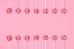 在两个小组和空的空间安排的许多五颜六色的棒棒糖candys在中心在桃红色背景 库存照片