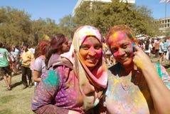 在两个微笑的夫人新春佳节的颜色粉末 免版税库存图片