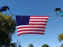在两个景气起重机勾子之间的美国国旗 图库摄影
