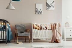 在两个木小儿床之间的减速火箭的扶手椅子在逗人喜爱的孪生托儿所 免版税库存照片
