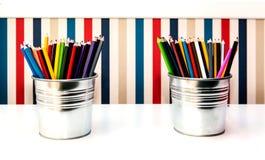 在两个桶的五颜六色的铅笔在背景 图库摄影
