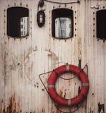 在两个窗口之间的Lifebuoy在木墙壁上 免版税库存图片