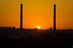 在两个管子的日落沃罗涅日工业区的能源厂之间 免版税库存图片