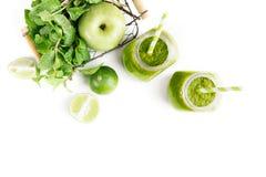 在两个金属螺盖玻璃瓶的绿色healty饮料用绿色苹果、薄菏和石灰在白色背景 素食食物概念 戒毒所 图库摄影