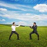 在两个年轻商人之间的争斗 免版税图库摄影