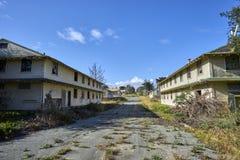 在两之间的长得太大和破裂的沥青街道离开了,被谴责的营房 库存照片