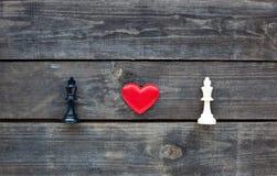 在两位棋国王之间的红色心脏土气木头的 免版税库存照片