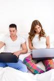 在两台便携式计算机上的偶然床夫妇在卧室 免版税库存照片