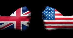 在两和美国绘的旗子英国在黑background/USA英国联系骗局握紧了面对的拳头 图库摄影