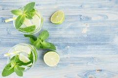 在两块湿玻璃的夏天凉快的柠檬水用薄菏,石灰,冰,在软的破旧的蓝色木板,拷贝空间,顶视图的秸杆 免版税库存图片
