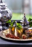 在两块玻璃和一个茶壶的摩洛哥薄荷的绿茶用新鲜薄荷和Sugarcubes 免版税图库摄影