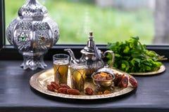 在两块玻璃和一个茶壶的摩洛哥薄荷的绿茶用新鲜薄荷和Sugarcubes 免版税库存图片