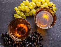 在两块玻璃顶部的照片与汁液,黑和绿色葡萄 库存照片