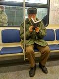 在两块玻璃中读书的老人坐在火车 免版税库存图片