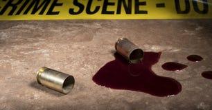 在两手枪壳和血液后的黄色犯罪现场磁带 图库摄影