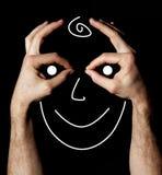 在两显示的标志之间的微笑的面孔好手 库存照片