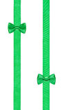 在两条平行的丝带的两个小的绿色弓结 免版税库存图片