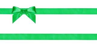 在两条平行的丝绸丝带的一个绿色弓结 免版税库存照片