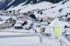 在两栏杆之间的积雪的灯笼与背景的山村房子 免版税库存图片