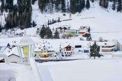 在两栏杆之间的积雪的灯笼与背景的山村房子 库存图片