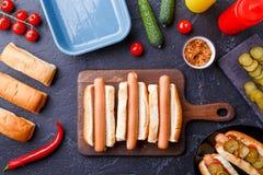 在两根热狗顶部的图片在桌上的切板用香肠 图库摄影