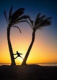 在两棵棕榈之间的人 免版税库存照片