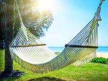 在两棵棕榈树之间的吊床在海滩 免版税库存图片