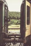 在两绿色和黄色火车无盖货车之间的老平台 库存照片