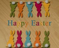 在两行的十只五颜六色的木复活节兔子在木地下 免版税库存照片