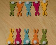 在两行的十只五颜六色的木复活节兔子在木地下 库存图片