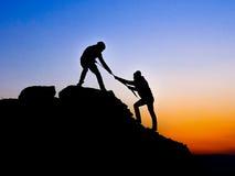 在两登山人之间的帮手 库存图片
