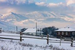 在两cotteges后的积雪的山 免版税库存图片