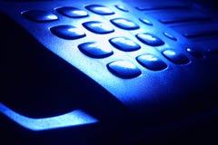 在严重的蓝色光的电话键盘 库存图片