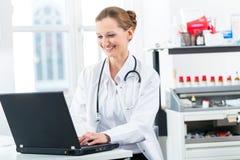 在个人计算机的女性医生文字在她的诊所 免版税库存照片