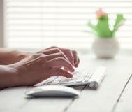 在个人计算机键盘的妇女手 图库摄影