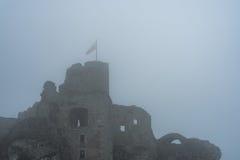 在中世纪城堡废墟顶部的旗子在大雾 免版税库存图片