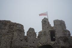 在中世纪城堡废墟顶部的旗子在大雾 免版税库存照片