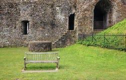 在中世纪墙壁废墟前面的一个长木凳 库存照片