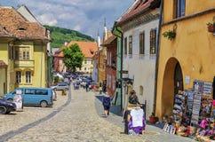 在中世纪街道上的游人在Sighisoara,罗马尼亚 免版税库存照片