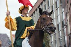 在中世纪衣裳的车手在一匹笑的马 免版税图库摄影