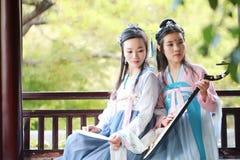 在中国传统古老服装戏剧负子蟾琵琶吉他的接近的女朋友bestie 免版税库存图片