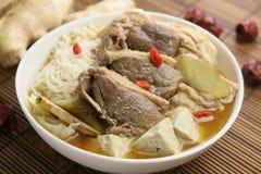在中国式的姜鸭子在竹盘子的白色罐 免版税库存照片