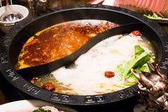 在中国式的shabu罐-猪肉汤和油腻的辣汤 图库摄影