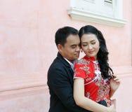 在中国式礼服的亚洲夫妇互相举行agianst桃红色墙壁 库存照片