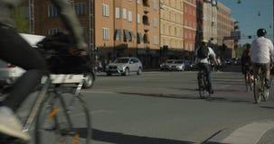 在中央斯德哥尔摩骑自行车横渡一个交叉点的通勤者 匿名人民在慢动作, 4K射击了 股票录像
