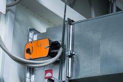 在中央通风系统的通风管安装的橙色制音器作动器 库存照片